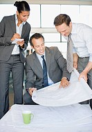 Architects reviewing blueprints together in office