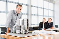 Architects in conference room with building model