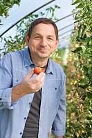 Germany, Saxony, Mature man tasting tomato at the farm, smiling, portrait