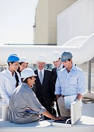 Worker talking to business people in hard_hats outdoors