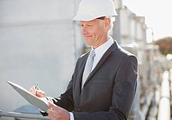 Businessman in hard_hat writing on clipboard outdoors