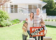 Family standing with sold sign of their new house (thumbnail)