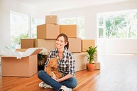 Woman sitting on floor of new house with teddy bear
