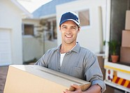Smiling man carrying box from moving van