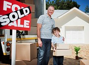 Father and son with boxes standing near sold sign for their new house