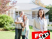 Realtor standing with family in front of new house (thumbnail)