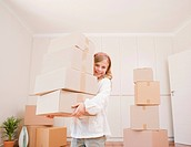 Girl carrying boxes in new house
