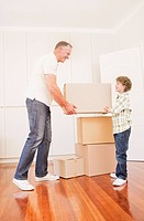 Father and son stacking boxes in new house