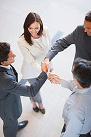 Business people holding hands together in office