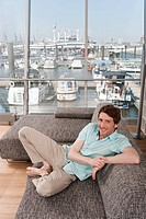 Germany, Hamburg, Man sitting on sofa and smiling