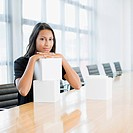 Businesswoman sitting in conference room with white cubes
