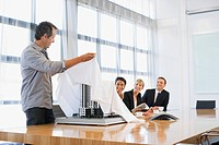 Businessman unveiling model building to co_workers