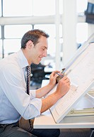 Businessman drawing on drafting table in office