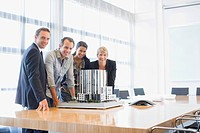Business people looking at model building in conference room