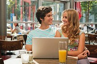 Germany, Munich, Couple with laptop in cafe