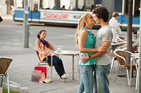 Germany, Munich, Couple kissing at cafe with woman in background