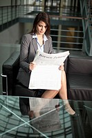 Germany, Bavaria, Business woman reading newspaper (thumbnail)