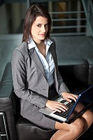 Germany, Bavaria, Business woman using laptop, portrait