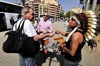 Dress Indian musician selling CD with Andean flute music. Gaudi square, Barcelona, Catalonia, Spain.