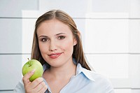 Germany, Cologne, Young woman with green apple, smiling, portrait