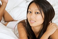 Asian woman in early 20´s laying in bed