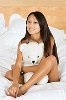 Asian woman in early 20´s setting in bed hugging a teddy bear