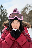 Young girl blowing on hand full of snow. Snowball. Ontario. Canada