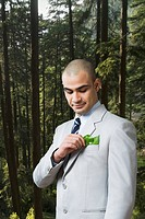 Businessman looking at a sapling in his pocket