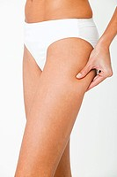 Young woman pinching thigh (thumbnail)
