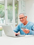 Senior man using laptop with credit card