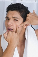 Man squeezing a pimple on his face