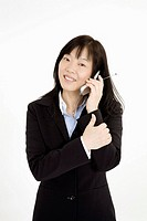 Beautiful Asain Businesswoman talking on a cell phone on a white background