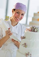 Portrait of happy young woman decorating wedding cake