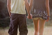 Rear view of a young couple outdoors, holding hands