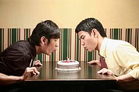 Two men blowing out candle on birthday cake