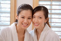 Women in bathrobes smiling at the camera