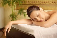 Woman lying on massage table with her eyes closed