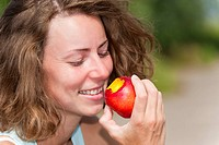 young woman eating a nectarine