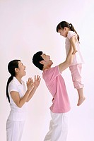 Man lifting girl up in the air, woman clapping