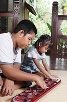 Boy and girl playing congkak together