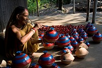 An elderly woman from the Hindu potter community paints clay wares at her yard Bogra, Bangladesh September 5, 2008