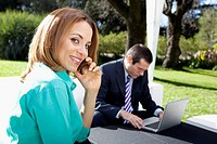 Businesswoman talking on a mobile phone with a businessman using a laptop