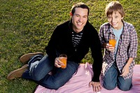 Portrait of a man enjoying picnic with his son
