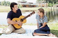 Man playing guitar with a woman sitting in front of him