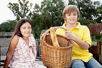 Girl sitting with her brother in a carriage with a picnic basket