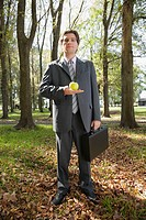 Businessman holding an apple in a forest