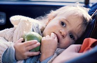 baby lying in the back seat of a car holding a green apple lost in thought