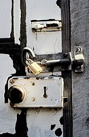 close up of a battered old door with three locks for extra security