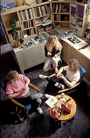 high angle view of three teenagers relaxing in a casual looking office space