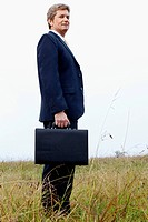 Businessman holding a briefcase and standing in a field